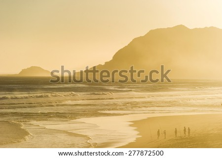 Silhouetted people standing on a beach during sunset. You can see fishing rods and the ocean is full of waves.  - stock photo