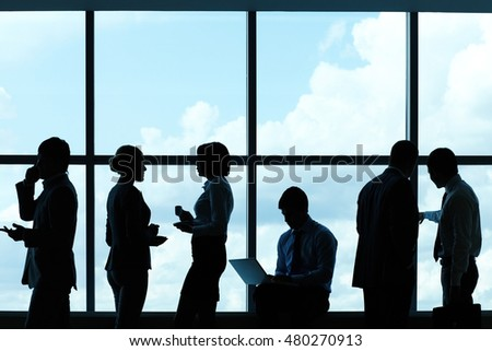 Silhouetted people working against the window in modern office