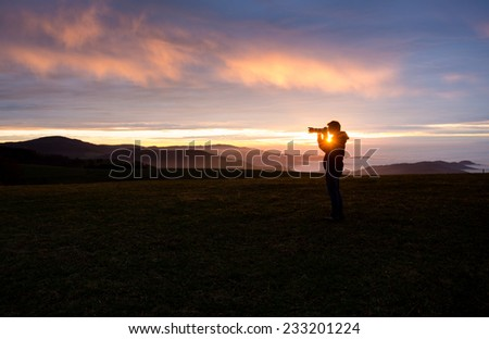 silhouetted photographer in sunset sky  - stock photo
