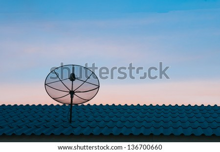 Silhouetted satellite dish on the roof in sunset sky