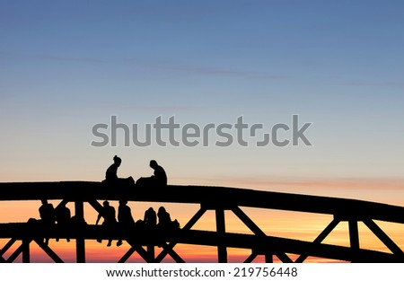 silhouetted teenagers sitting on bridge in sunset