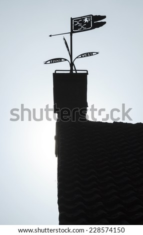 Silhouetted weather vane on a chimney stack pointing east - stock photo