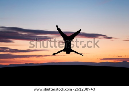 silhouetted young man jumping upside down in sunset