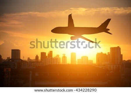 Silhouettes airplane on sunset in the city background - stock photo