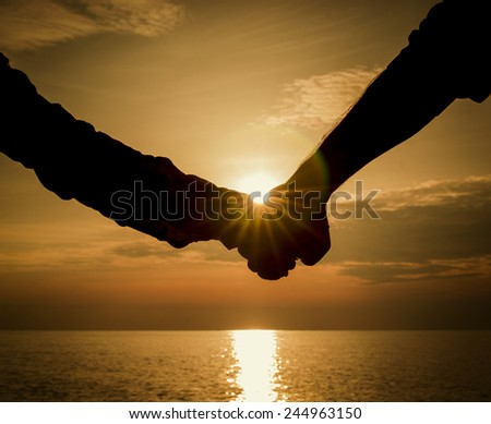Silhouettes couples hands on sunset - stock photo