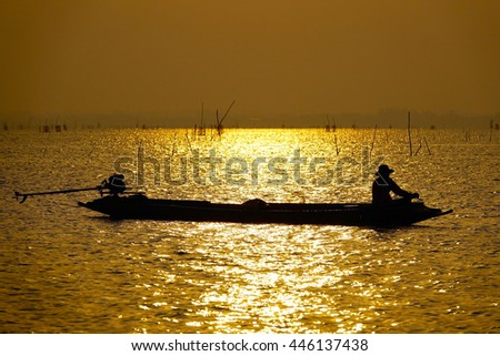 silhouettes fishermen working on little colorful boat in golden lake at sunrise time,select focus with shallow depth of field.