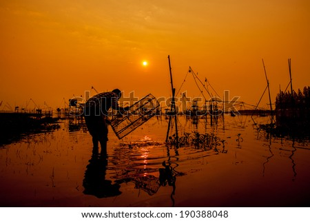 Silhouettes fishing net fishing Thailand. - stock photo