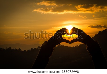 Silhouettes hand heart shaped with sunsets and the sky orange