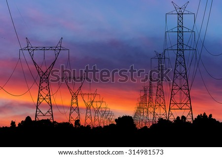 Silhouettes high voltage transmission towers on field.