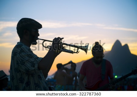 Silhouettes in defocus of a musician playing his horn to an audience at the popular Arpoador sunset spot near Ipanema Beach in Rio de Janeiro Brazil