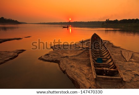 Silhouettes landscape view sunset and old wooden boats in mekong river ubon ratchathani province thailand - stock photo