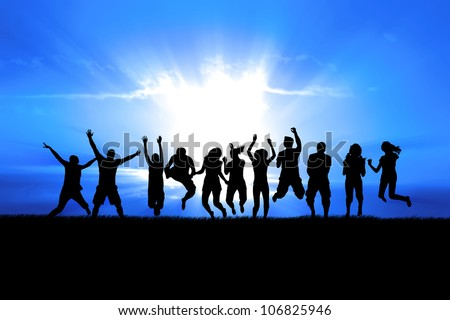 Silhouettes of a celebratory group jump in field of grass, bright sun behind
