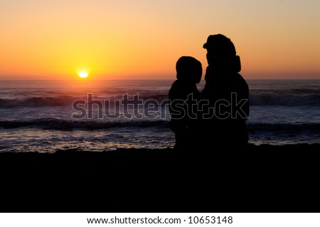 Silhouettes of a child and her mother watching sunset at Pacific ocean beach in California.