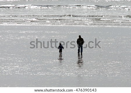 Silhouettes of a man and child on a beach at low tide, Penzance, Cornwall, England, UK.