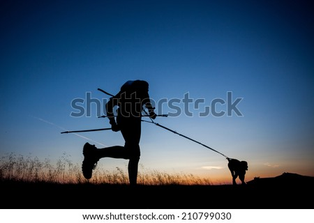 Silhouettes of a runner and a his dog during a sunrise - stock photo