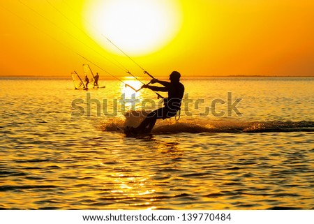 Silhouettes of a windsurfers sailing in the gulf at sunset  - stock photo