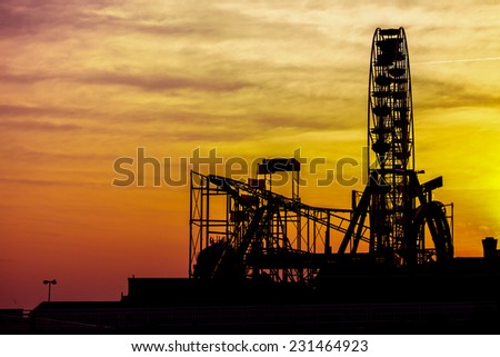 Silhouettes of amusement park at sunset