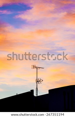 Silhouettes of antennas backlit at sunset with colorful sky clouds - stock photo