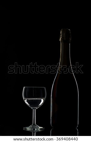Silhouettes of bottles of sparkling wine and champagne glasses on a black background, studio lighting