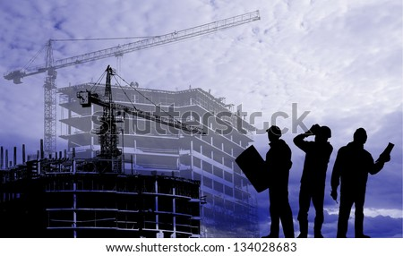 Silhouettes of builders on a background of houses under construction