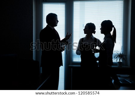 silhouettes of business partners discuss against the window in the office - stock photo