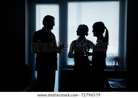 silhouettes of business partners discuss against the window in the office