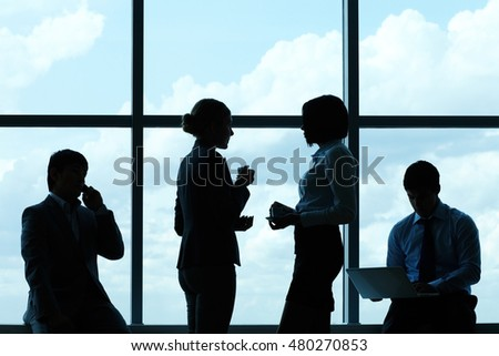 Silhouettes of business people against the window