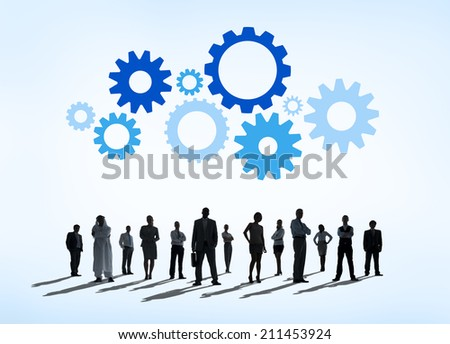 Silhouettes of Business People and Gears Above - stock photo