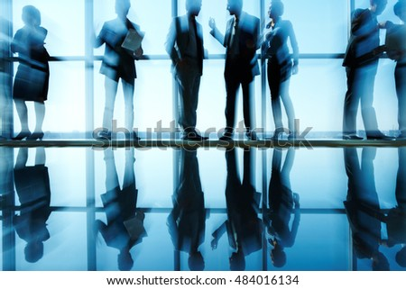 Silhouettes of business people lit from behind and their reflection in the floor