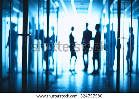 Silhouettes of business people standing in corridor of business center - stock photo