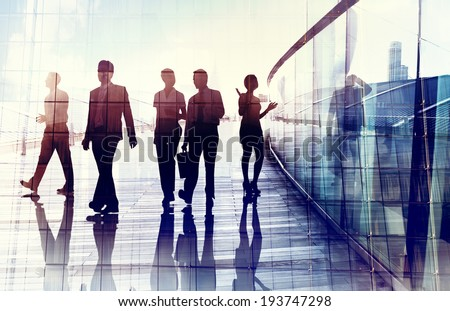 Silhouettes of Business People Walking in the Office - stock photo