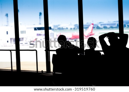 Silhouettes of businessman and passengers traveling on airport, waiting at the plane boarding gates. - stock photo