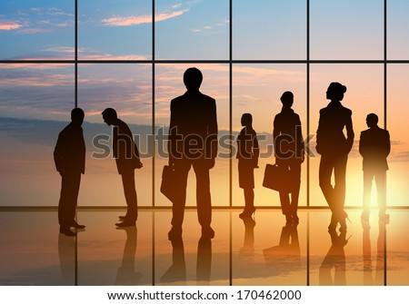 Silhouettes of businesspeople standing against panoramic office window - stock photo
