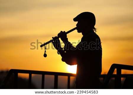 Silhouettes of busker playing a flute on the Bridge (long exposure)