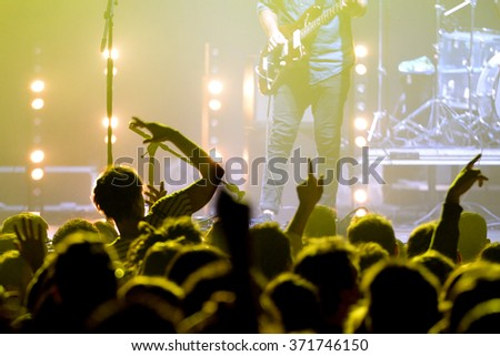 Silhouettes of cheering crowd at concert - stock photo