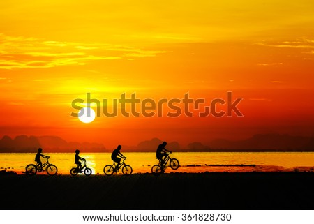 Silhouettes of childrens on bicycle against sunset sky at the beach. - stock photo