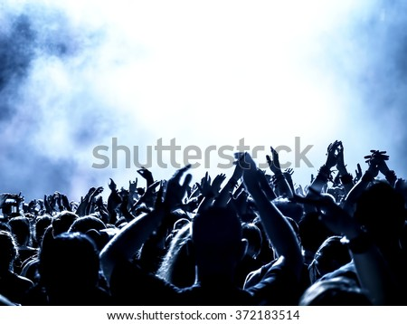 silhouettes of concert crowd in front of bright stage lights - no fine details due limited light situation - stock photo