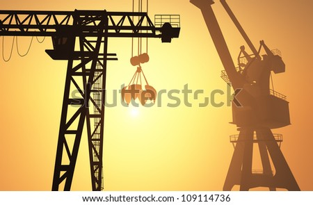 Silhouettes of construction cranes against the evening sky. .