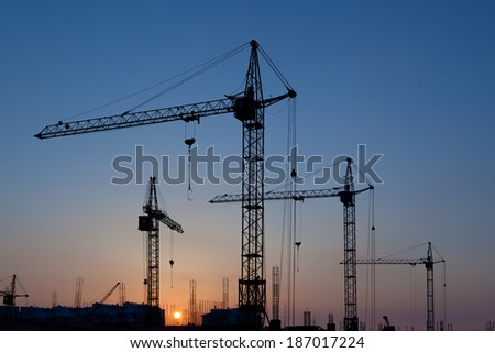 Silhouettes of construction cranes against the sky - stock photo