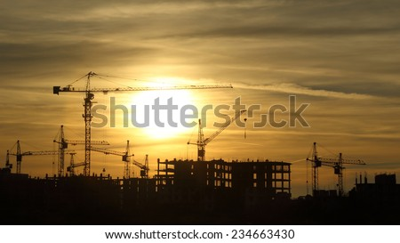 silhouettes of construction cranes at sunset - stock photo