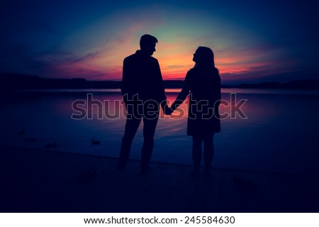 Silhouettes of couple against the sunset sky. Vintage photo. - stock photo