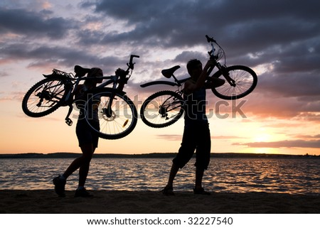 Silhouettes of couple carrying their bikes while walking down seashore at sunset - stock photo