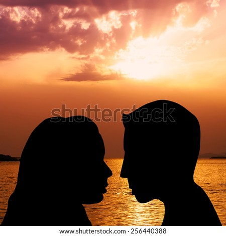 Silhouettes of couple kissing on the beach at sunset - stock photo