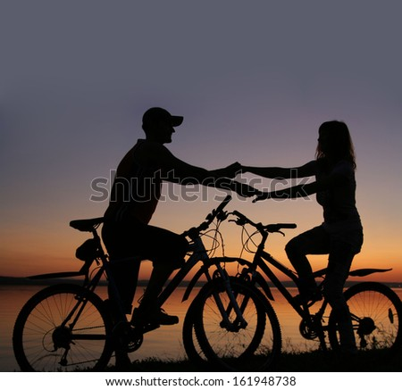 Silhouettes of couple opposite each other on their bicycles by the sea at sunset drawn to each other