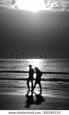 Silhouettes of couple walking along a beach at dramatic sunset and talking. Crisis in relations background. Aged photo. Black and white.