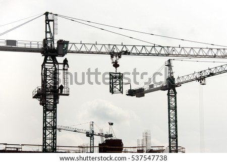 Silhouettes of cranes with a load on the construction of buildings against the evening sky