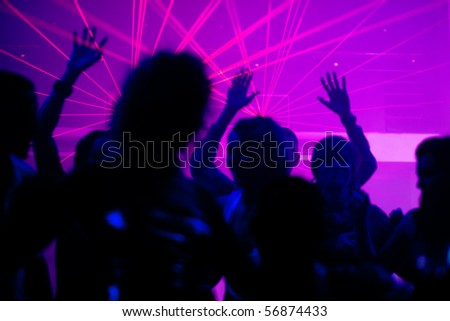 Silhouettes of dancing people having a celebration in a disco club, the light show is sending laser beams through the backlit scene, FOCUS IN ON THE BEAMS! - stock photo