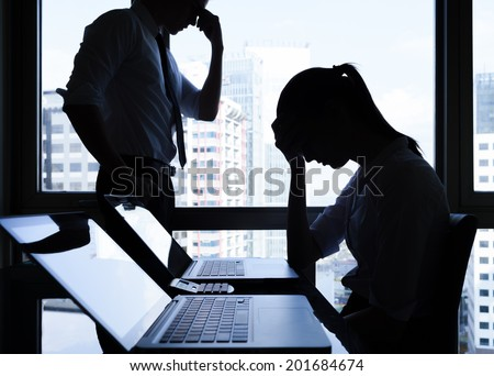 Silhouettes of depressed business people in the office. - stock photo