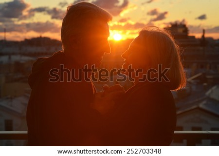 Silhouettes of elderly couple in love over sunset sky - stock photo