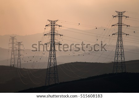 Silhouettes of electric towers in the foggy morning.